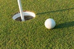 Sfera di golf sull'orlo della tazza Immagini Stock Libere da Diritti