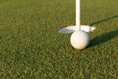 Sfera di golf sull'orlo della tazza Fotografie Stock Libere da Diritti
