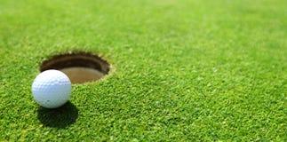 Sfera di golf sull'orlo della tazza