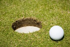 Sfera di golf vicino ad un foro Immagini Stock Libere da Diritti