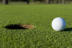 Sfera di golf vicino al foro Immagini Stock