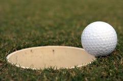 Sfera di golf vicino alla tazza Fotografia Stock