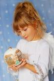 Sfera di natale della holding della ragazza di angelo a disposizione Fotografia Stock