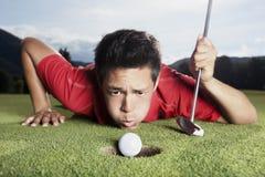 Sfera di salto del giocatore di golf nella tazza. Fotografie Stock Libere da Diritti