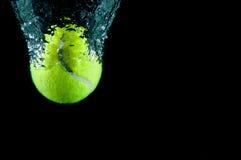Sfera di tennis che accelera attraverso l'acqua fotografie stock libere da diritti