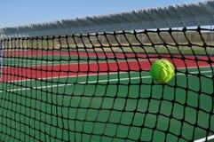 Sfera di tennis gialla che colpisce la rete Immagine Stock