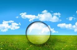 Sfera di vetro in un campo di erba Fotografie Stock