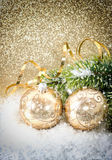 Sfera dorata di natale con la filiale dell'albero di Natale Immagine Stock