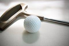 Sfera e putter di golf su bianco Fotografia Stock