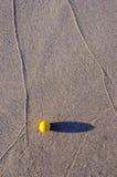 Sfera gialla sulla sabbia della spiaggia del mare Fotografia Stock