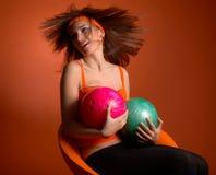 Sfere di bowling della holding della giovane donna immagini stock