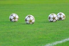 Sfere di calcio nel campo verde Fotografia Stock