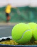 Sfere di tennis sulla racchetta e su una persona nella priorità bassa Fotografie Stock Libere da Diritti