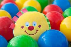 Sfere variopinte con il giocattolo sorridente del fronte nella metà Immagini Stock