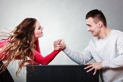 Sfida di braccio di ferro fra le giovani coppie immagini stock