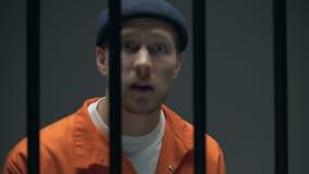 Sfida di lancio del prigioniero arrogante, guardante alla macchina fotografica, criminale pericoloso video d archivio