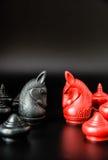 Sfida nera e rossa del pezzo degli scacchi di Thai del cavaliere su fondo nero e sul fuoco selettivo Fotografia Stock