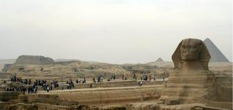 Sfinxen och de stora pyramiderna av den Giza platån på skymning Arkivfoto