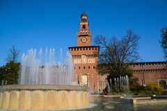 Sforza Castle with Fountain, Milan, Italy. Sforza Castle in Milan, Italy, with circular fountain. Brick building, trees, and blue sky royalty free stock image