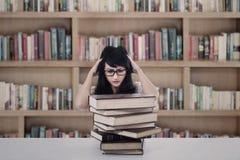 Sforzo attraente della studentessa che esamina i libri in biblioteca Fotografia Stock Libera da Diritti
