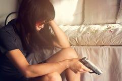 Sforzo della donna e deprimente della sua malattia, ha deciso di uccidersi con una pistola a disposizione Immagini Stock Libere da Diritti
