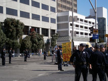 SFPD Police officers stand on street as protesters hold sign say Stock Photos
