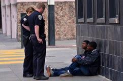 SFPD-tjänstemän som förhör svarta amerikanska män i San Francisco Royaltyfri Bild