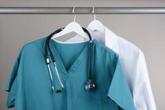 Sfrega con lo stetoscopio ed il cappotto del laboratorio sul gancio Fotografie Stock Libere da Diritti