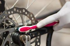 Sfregamento bianco d'uso dello spazzolino da denti della tenuta del guanto della mano del primo piano sulla catena della biciclet Fotografie Stock