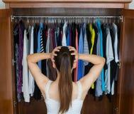 Sfrustowana młoda kobieta no może decydować co być ubranym od jej szafy zdjęcia stock