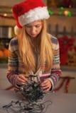 Sfrustowana nastoletnia dziewczyna w Santa kapeluszowych untangling bożonarodzeniowe światła Fotografia Stock