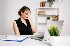 Sfrustowany ?e?ski pracownik w biurowym ather biurku zm?czona choroby kobieta obrazy stock