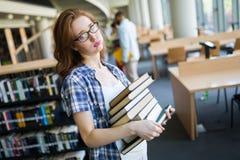 Sfrustowany żeński uczeń z ogromnym stosem nauk książki Martwiący się o egzaminach obraz stock
