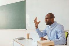 Sfrustowany amerykanin afrykańskiego pochodzenia nauczyciel gestykuluje i siedzi przy biurkiem fotografia royalty free