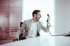 Sfrustowany biznesmen wrzeszczy przy telefonem fotografia royalty free