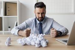 Sfrustowany biznesmena obsiadanie przy miejscem pracy z zmiętymi papierami na nim zdjęcia stock