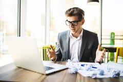 Sfrustowany biznesowy mężczyzna na biurku z papierem i laptopem jest stresujący się gniewny zdjęcia royalty free