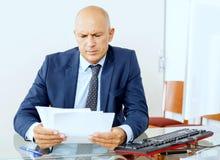 Sfrustowany biznesowy mężczyzna pracuje przy biurem zdjęcia royalty free