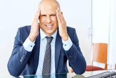 Sfrustowany biznesowy mężczyzna pracuje przy biurowym wnętrzem zdjęcia royalty free