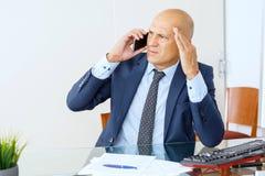 Sfrustowany biznesowy mężczyzna pracuje przy biurowym wnętrzem zdjęcie stock