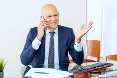Sfrustowany biznesowy mężczyzna pracuje przy biurowym wnętrzem obraz stock