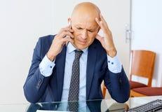 Sfrustowany biznesowy mężczyzna pracuje przy biurowym wnętrzem zdjęcie royalty free