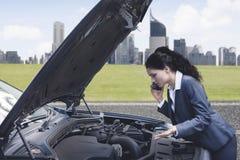 Sfrustowany bizneswoman z jej łamanym samochodem fotografia royalty free