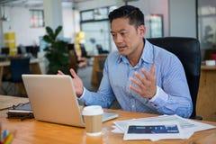 Sfrustowany dyrektor wykonawczy patrzeje laptop zdjęcia stock