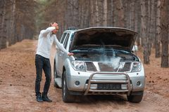 Sfrustowany facet, stoi blisko łamanego samochodu z otwartym kapiszonem z dymem, stoi i chwyty przewodzą obrazy stock