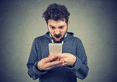 Sfrustowany gniewny mężczyzna czyta wiadomość tekstową na jego smartphone uczuciu udaremniającym zdjęcie royalty free