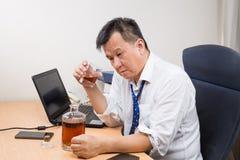 Sfrustowany i stresujący Azjatycki kierownik pije ciężkiego trunek w o obraz stock
