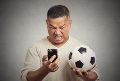 Sfrustowany mężczyzna patrzeje na komórka telefonu mądrze dopatrywania mienia gemowym futbolu Obraz Stock