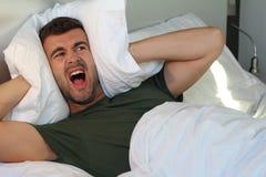 Sfrustowany mężczyzna zakrywa jego ucho z poduszką zdjęcia royalty free
