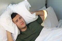Sfrustowany mężczyzna zakrywa jego ucho z poduszką fotografia royalty free